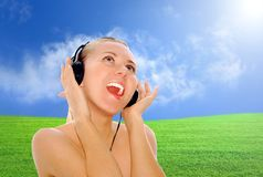 Happiness women in headphones and listening music. Portrait of happiness young women with beautiful face in headphones and listening music on the blue sky and royalty free stock images