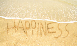 Happiness written in the sand Stock Photography