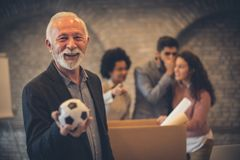 Happiness is when you do what you love. Businesspeople in the office. Man holding football ball. Focus on man stock image