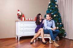 Happiness young adult couple in love celebrating christmas. holidays and celebration concept. Looking at each other and toothy smile. Indoor, studio shot Stock Images