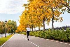 Happiness young adult girl jogging in autumn park, looking at ca Stock Photo