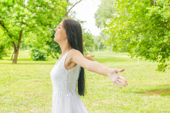 Happiness young woman enjoyment in the nature. Happiness young woman with sprading hands enjoyment in the nature and beautiful day Stock Photo