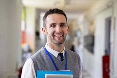 Happly-Lehrer Standing im Korridor Lizenzfreie Stockbilder
