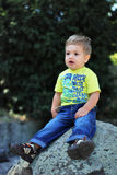Happly little boy. Portrait with gorgeous little boy sitting on a big stone Royalty Free Stock Photography