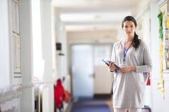 Happly Teacher Standing in Corridor Stock Image