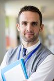 Happly Teacher Standing in Corridor Stock Photography
