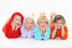 Happpy children in bathrobe. Four happy children lying down on a belly,dressed in bathrobe Royalty Free Stock Photo