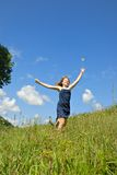 HAPPY. Excited girl running in a green field with her hands in the air tossing a flower against a blue sky Royalty Free Stock Image