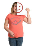 Happy. A happy smiling girl is holding up a white piece of paper with half a happy face on it Stock Photo