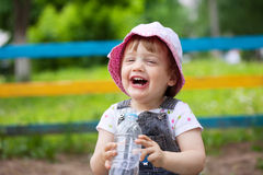 Happy  2 years baby drinks from  bottle. Happy  2 years baby with plastic bottle in park Stock Image