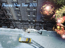 Happy 2011. A yellow taxi stops close to the entrance of a building, under the snow Royalty Free Stock Images