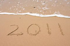Happy 2011 - Happy New Year. Written in the sand at the beach Royalty Free Stock Photo