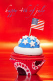 Happy 4th of july. And a cupcake decorated with the colors and stars of United States flag stock images
