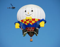 Happy. Hot air balloon with a helicopter circling it in albuquerque new Mexico Stock Image