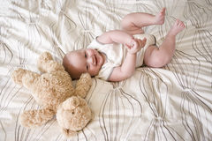 Happy 7 month old baby lying next to teddy bear Royalty Free Stock Image