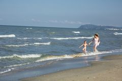 Happy beautiful mom and child run along the sea beach, copy-space Royalty Free Stock Image