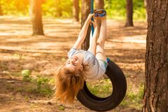 Happy active child girl playing on swing wheel in forest on sunny summer day. Preschool child having fun and swinging on a tire
