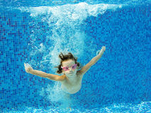 Happy active child jumps to swimming pool. Kids sport on summer vacation, underwater swimming and fun in pool stock photo