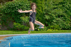 Happy active child jumps to swimming pool Royalty Free Stock Photography