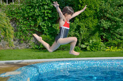 Happy active child jumps to swimming pool Stock Images