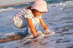 Happy active child splashing and playing in sea. Stock Image