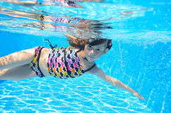 Happy active child swims freestyle in pool, underwater view. Girl having fun on family summer vacation, kids sport concept Royalty Free Stock Photos