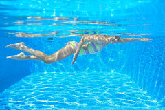 Happy active child swims freestyle in pool, underwater view Stock Photography