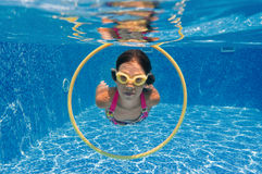 Happy active child swims underwater in pool Royalty Free Stock Photo
