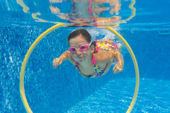 Happy active child swims underwater in pool Royalty Free Stock Photos