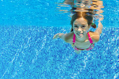 Happy active child swims underwater in pool Stock Image