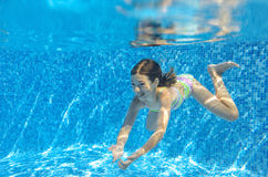 Happy active child swims underwater in pool Stock Images