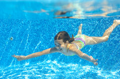 Happy active child swims underwater in pool Stock Photo