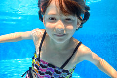 Happy active child swims underwater in pool Stock Photography
