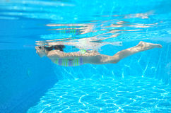 Happy active child swims underwater in pool Royalty Free Stock Image