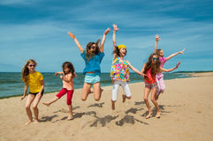 Happy active children jumping on the beach Stock Image