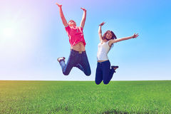 Happy active couple jumping in green field against blue sky Royalty Free Stock Photos