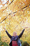 Happy active elderly woman. A smiling elderly 75 year old woman under autumn tree with arms up royalty free stock photo