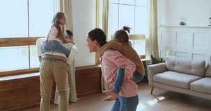 Happy active family parents piggyback children playing in living room
