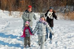 Happy family walks in winter, having fun and playing with snow outdoors on holiday weekend royalty free stock photo