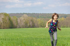 Happy active girl running on green field Royalty Free Stock Photos
