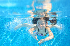 Happy active girl swims underwater in pool Stock Photos