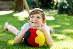 Happy active kid boy playing soccer with ball in German flag colors. Healthy child having fun with football game and. Action outdoors Royalty Free Stock Photo