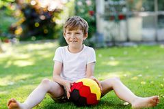 Happy active kid boy playing soccer with ball in German flag colors. Healthy child having fun with football game and. Action outdoors Stock Image