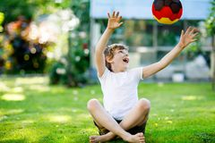 Happy active kid boy playing soccer with ball in German flag colors. Healthy child having fun with football game and. Action outdoors Stock Images