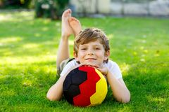 Happy active kid boy playing soccer with ball in German flag colors. Healthy child having fun with football game and. Action outdoors Stock Photos