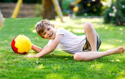 Happy active kid boy playing soccer with ball in German flag colors. Healthy child having fun with football game and. Action outdoors Royalty Free Stock Images