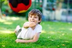 Happy active kid boy playing soccer with ball in German flag colors. Healthy child having fun with football game and. Action outdoors Royalty Free Stock Photos