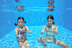 Happy active kids swim in pool and play underwater. Girls diving and having fun, children on summer vacation, sport concept stock photography