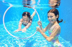 Happy active kids swim in pool and play underwater. Girls diving and having fun, children on summer  vacation, sport concept Royalty Free Stock Photo