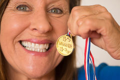 Happy active mature woman with medal Royalty Free Stock Images